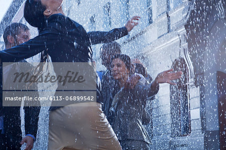Business people dancing in rain Stock Photo - Premium Royalty-Free, Image code: 6113-06899542