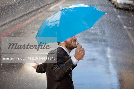 Businessman with tiny umbrella walking in rain Stock Photo - Premium Royalty-Free, Image code: 6113-06899543