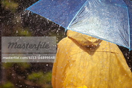 Woman under umbrella in rain Stock Photo - Premium Royalty-Free, Image code: 6113-06899548