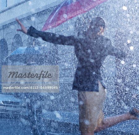 Businesswoman dancing in rain Stock Photo - Premium Royalty-Free, Image code: 6113-06899549