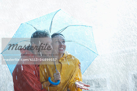 Happy couple under umbrella in rain Stock Photo - Premium Royalty-Free, Image code: 6113-06899557