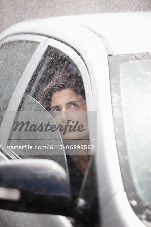 Businesswoman in car looking up at rain Stock Photo - Premium Royalty-Free, Image code: 6113-06899562