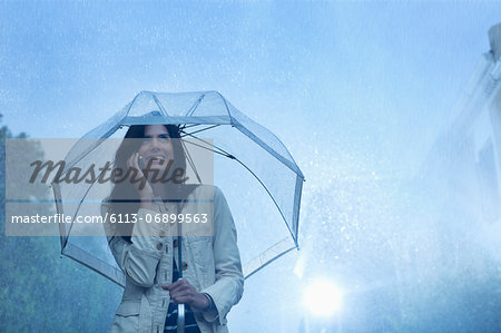 Businesswoman talking on cell phone under umbrella in rain Stock Photo - Premium Royalty-Free, Image code: 6113-06899563