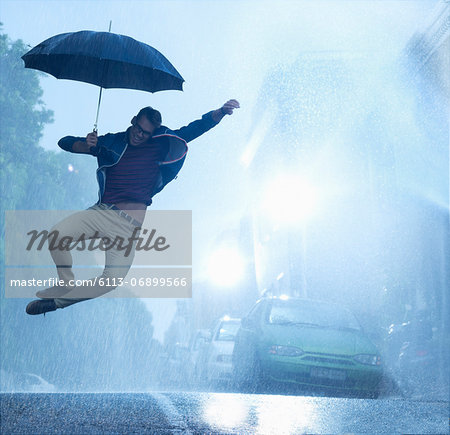 Enthusiastic man with umbrella jumping in rain Stock Photo - Premium Royalty-Free, Image code: 6113-06899566