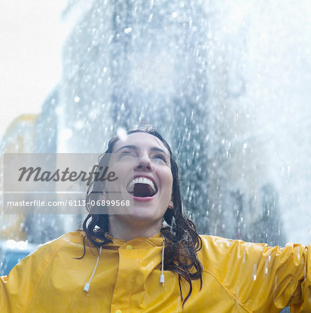 Enthusiastic woman standing in rain Stock Photo - Premium Royalty-Free, Image code: 6113-06899568