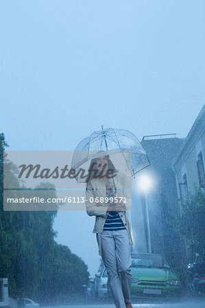 Happy woman with umbrella walking in rain Stock Photo - Premium Royalty-Free, Image code: 6113-06899571