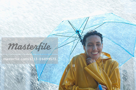 Happy woman under umbrella in rain Stock Photo - Premium Royalty-Free, Image code: 6113-06899573