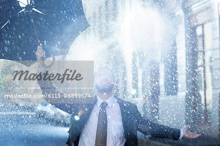 Enthusiastic man with broken umbrella in rain Stock Photo - Premium Royalty-Free, Image code: 6113-06899574
