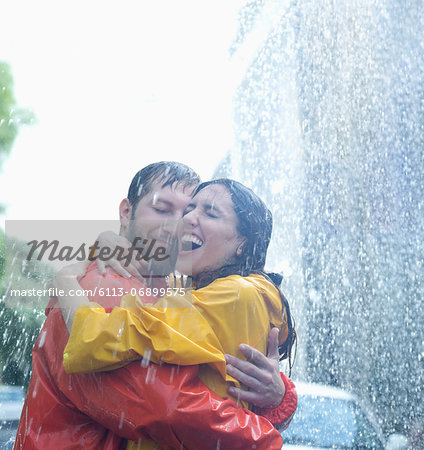 Happy couple hugging in rain Stock Photo - Premium Royalty-Free, Image code: 6113-06899575