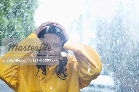 Happy woman with hands on head in rain Stock Photo - Premium Royalty-Free, Image code: 6113-06899577