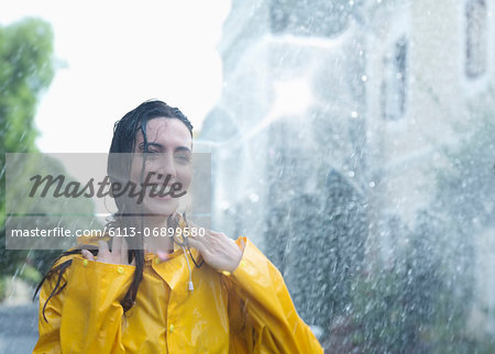 Enthusiastic woman standing in rain Stock Photo - Premium Royalty-Free, Image code: 6113-06899580