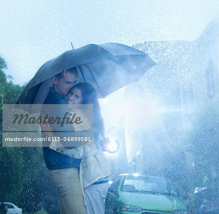 Happy couple hugging under umbrella in rain Stock Photo - Premium Royalty-Free, Image code: 6113-06899581