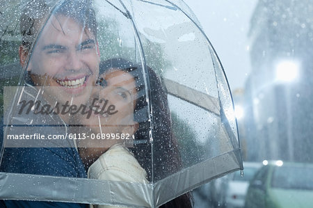 Happy couple hugging under umbrella in rain Stock Photo - Premium Royalty-Free, Image code: 6113-06899582