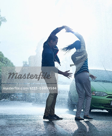 Happy couple dancing in rain Stock Photo - Premium Royalty-Free, Image code: 6113-06899584