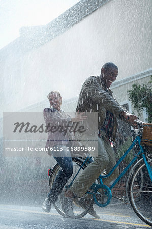 Happy couple riding bicycle in rainy street Stock Photo - Premium Royalty-Free, Image code: 6113-06899589