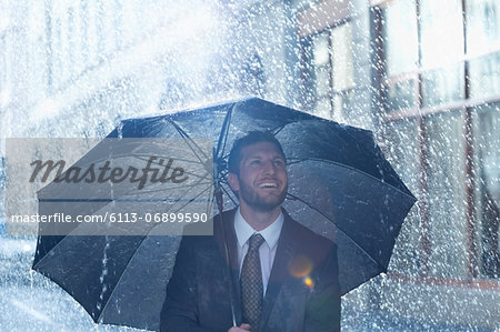 Happy businessman under umbrella in rain Stock Photo - Premium Royalty-Free, Image code: 6113-06899590