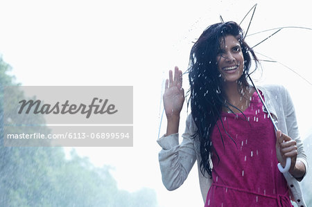 Portrait of smiling woman under umbrella in rain Stock Photo - Premium Royalty-Free, Image code: 6113-06899594