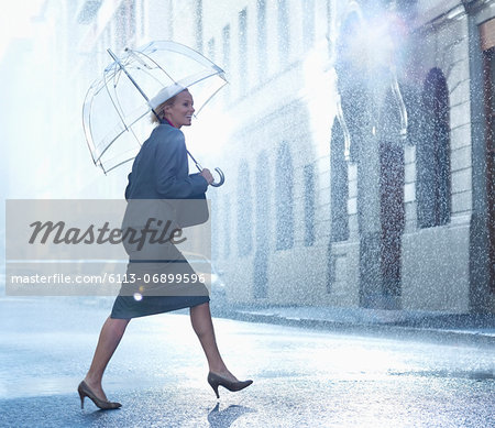 Happy businesswoman with umbrella walking across rainy street Stock Photo - Premium Royalty-Free, Image code: 6113-06899596
