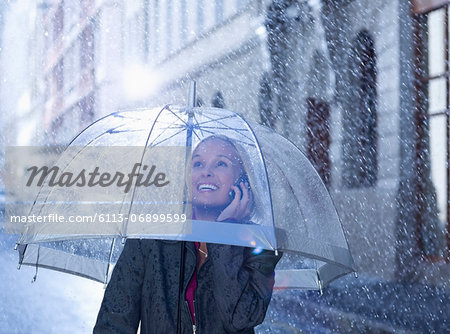 Smiling businesswoman talking on cell phone under umbrella in rainy street Stock Photo - Premium Royalty-Free, Image code: 6113-06899599
