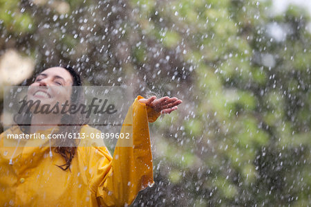 Happy woman standing with arms outstretched in rain Stock Photo - Premium Royalty-Free, Image code: 6113-06899602