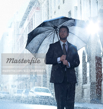 Businessman under umbrella in rainy street Stock Photo - Premium Royalty-Free, Image code: 6113-06899604