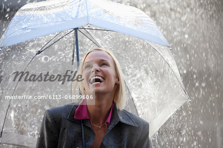 Laughing businesswoman under umbrella in rain Stock Photo - Premium Royalty-Free, Image code: 6113-06899606