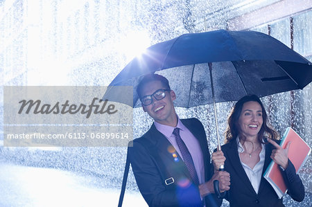 Happy businessman and businesswoman walking under umbrella in rain Stock Photo - Premium Royalty-Free, Image code: 6113-06899614