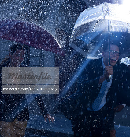 Happy business people running with umbrellas in rain Stock Photo - Premium Royalty-Free, Image code: 6113-06899615