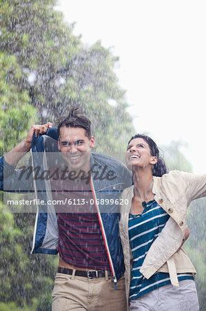 Happy couple walking in rain Stock Photo - Premium Royalty-Free, Image code: 6113-06899620