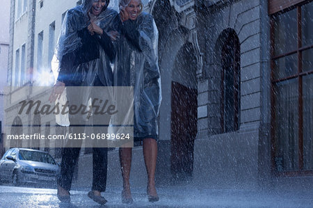 Businesswomen in ponchos walking in rainy street Stock Photo - Premium Royalty-Free, Image code: 6113-06899624