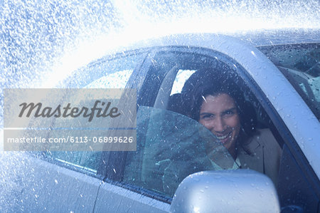 Portrait of smiling businesswoman inside car in rain Stock Photo - Premium Royalty-Free, Image code: 6113-06899626