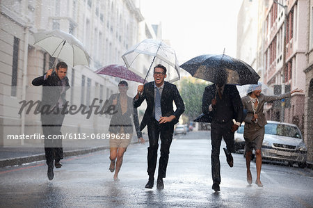 Business people with umbrellas running in rainy street Stock Photo - Premium Royalty-Free, Image code: 6113-06899628