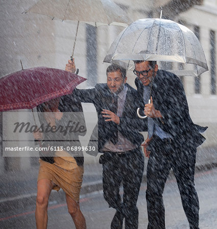 Happy business people with umbrellas running in rainy street Stock Photo - Premium Royalty-Free, Image code: 6113-06899630