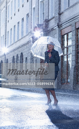 Businesswoman under umbrella in rainy street Stock Photo - Premium Royalty-Free, Image code: 6113-06899634