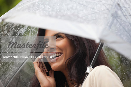 Happy woman talking on cell phone under umbrella in rain Stock Photo - Premium Royalty-Free, Image code: 6113-06899642