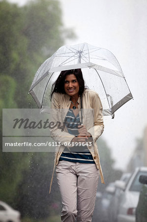 Happy woman under umbrella in rain Stock Photo - Premium Royalty-Free, Image code: 6113-06899643