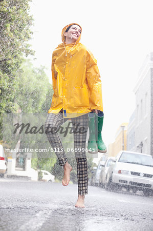 Happy woman dancing barefoot in rainy street Stock Photo - Premium Royalty-Free, Image code: 6113-06899645