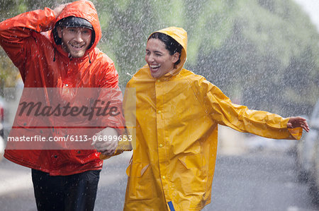 Happy couple holding hands and running in rainy street Stock Photo - Premium Royalty-Free, Image code: 6113-06899653
