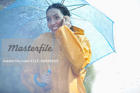 Happy woman talking on cell phone under umbrella in rain Stock Photo - Premium Royalty-Free, Image code: 6113-06899654