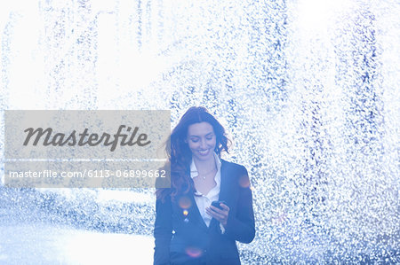 Happy businesswoman text messaging with cell phone in rain Stock Photo - Premium Royalty-Free, Image code: 6113-06899662