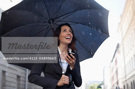Happy businesswoman text messaging with cell phone under umbrella in rain Stock Photo - Premium Royalty-Free, Image code: 6113-06899663