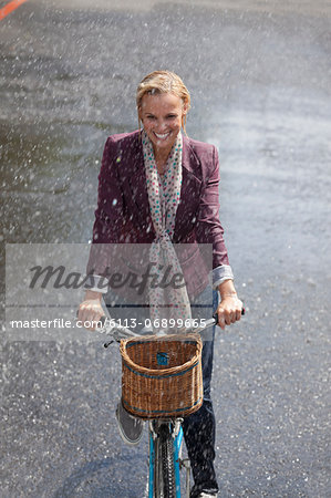 Happy woman riding bicycle in rainy street Stock Photo - Premium Royalty-Free, Image code: 6113-06899665