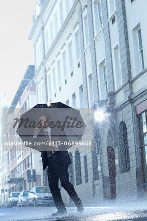 Businessman talking on cell phone under umbrella in rainy street Stock Photo - Premium Royalty-Free, Image code: 6113-06899668