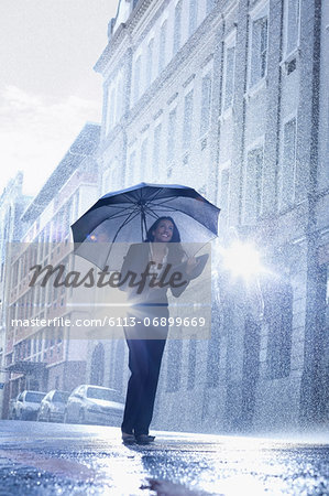 Businesswoman standing under umbrella in rainy street Stock Photo - Premium Royalty-Free, Image code: 6113-06899669