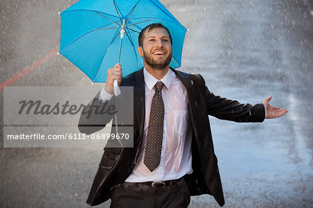 Enthusiastic businessman with tiny umbrella in rainy street Stock Photo - Premium Royalty-Free, Image code: 6113-06899670