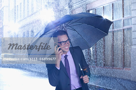 Happy businessman talking on cell phone under umbrella in rainy street Stock Photo - Premium Royalty-Free, Image code: 6113-06899677