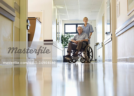 Nurse wheeling older patient in hospital Stock Photo - Premium Royalty-Free, Image code: 6113-06908192