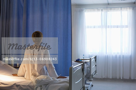 Patient wearing gown on hospital bed Stock Photo - Premium Royalty-Free, Image code: 6113-06908243