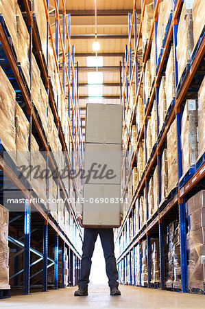 Worker holding boxes in warehouse Stock Photo - Premium Royalty-Free, Image code: 6113-06908391