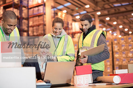 Businesswoman and workers using laptop in warehouse Stock Photo - Premium Royalty-Free, Image code: 6113-06908436